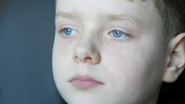Tvář krásné teenager s pihy zblízka. Chlapec s modrýma očima při pohledu do dálky