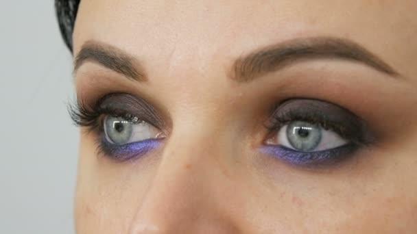 Krásné drahé stylové večerní make-up kouřové oči neobvyklé šedé a modré odstín očních stínů. Krásná žena modré oči zavřít pohled