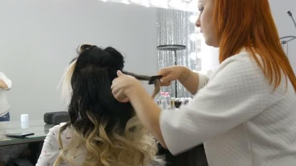 Profesionální kadeřník stylista dělá účes s lak na vlasy pro krásnou mladou ženu s dlouhými vlasy barvené ombre technikou v kosmetickém studiu