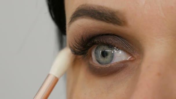 Profesionální make-up. Stylista make-up umělec aplikuje make-up na mladou ženu se speciálním štětcem v salonu krásy