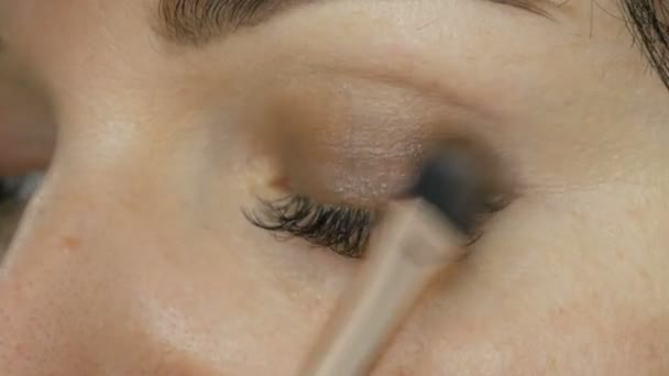 Oční make-up speciálním štětcem. Detailní záběr modré barvy s dlouhými řasami