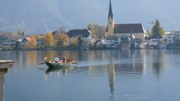 eine schifffähre fähre die menschen auf die andere seite, im hintergrund der schönen, malerischen kirche am tegernsee, bayern, deutschland
