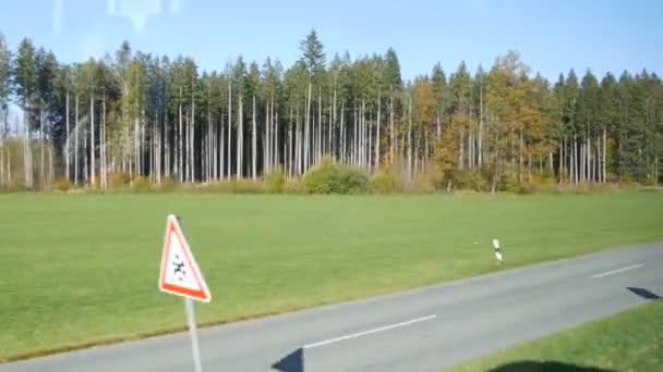 Pohled z okna vlaku na procházející bavorské vesnice a přírodu. Stromy procházející krajinou z okna vlaku