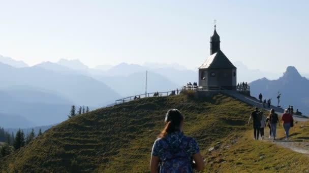Tegernsee, Německo - 23. října 2019: Starý kostel na krásném malebném svahu Bavorských Alp, poblíž kterého se procházejí turisté
