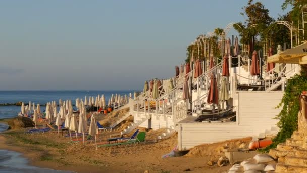 Luxury vacation at Black Sea, Bulgaria. Empty multi-colored sun loungers or sunbeds and folded beach umbrellas on resort beach
