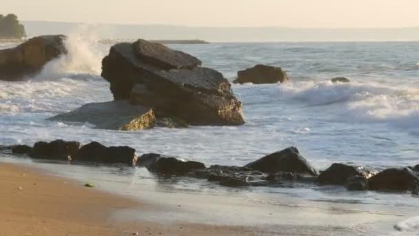 Hajnal a tengeren. Gyönyörű nagy viharos hullámok hab fedi hatalmas sziklák és sziklák a parton, Extreme Wave zúzó partján