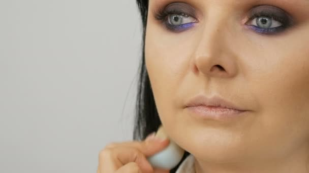 Stylist makeup artist applies foundation for face with a special brush on the face of young beautiful woman with blue eyes