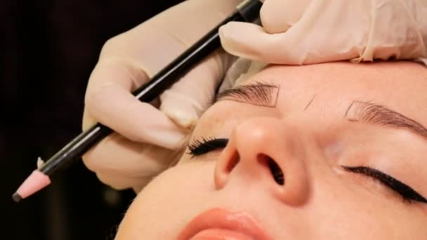 A kozmetikus szemöldökkorrekciót végez a betegén. A szemöldök körvonalának megjelölése speciális ceruzával