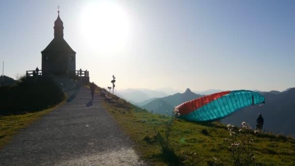 Tegernsee, Německo - 23. října 2019: Starý kostel na krásném malebném svahu Bavorských Alp, poblíž kterého se procházejí turisté, Horská paragliding