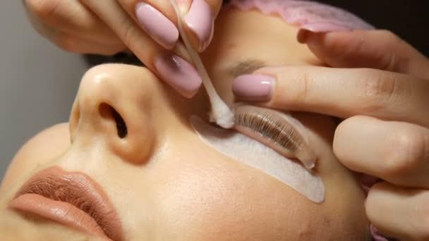Kosmetikerin entfernt spezielle Wellness-Botox-Mischung und molekulare Wiederherstellung auf Wimpern Nahsicht. Professionelles Verfahren für Laminierung und Botox-Wimpern.