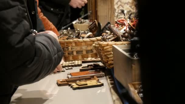 Hände von Menschen spielen mit Holzspielzeug für die Logik im Kiosk auf dem Weihnachtsmarkt in München. deutsche Inschrift