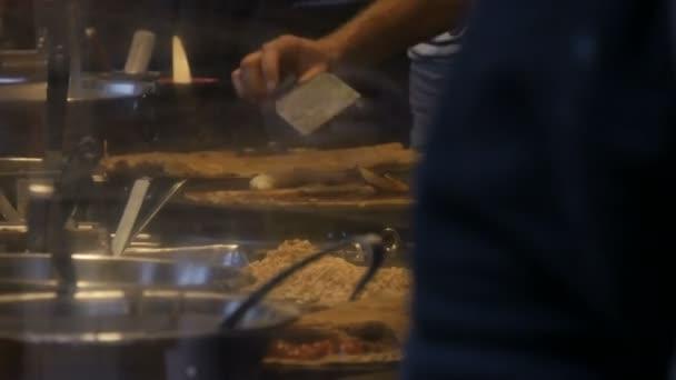 Kuchaři ruce v stánku s rychlým občerstvením připravují omelety, palačinky, nudle a další lahodná jídla. Boční pohled na ženy a muže vaří čtyři ruce