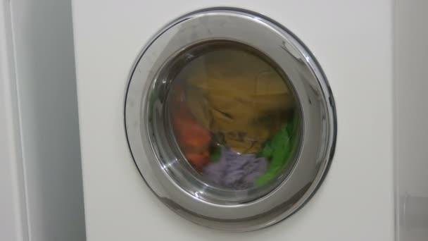 A többszínű ruhákat egy fehér mosógépben mossák a mosókonyhában..