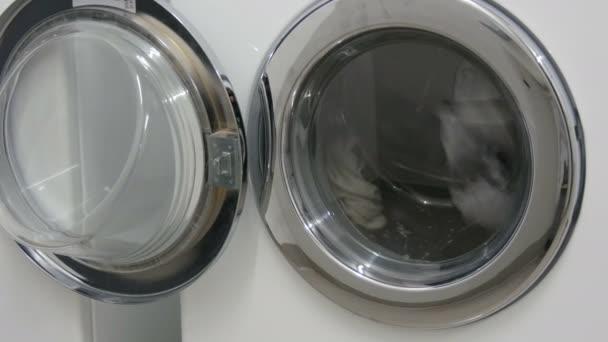 schwarze und weiße Kleidung. Wäsche wird in einer weißen Waschmaschine in der Wäscherei gewaschen.