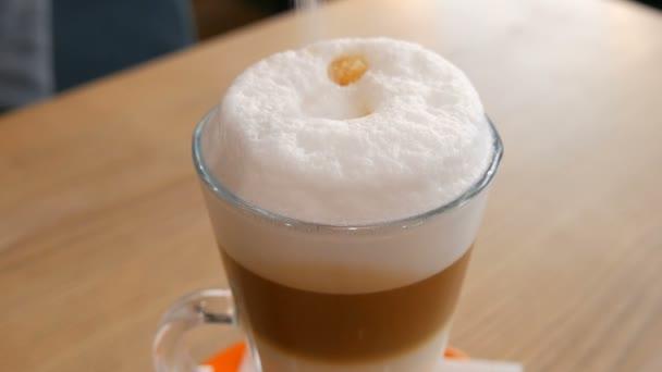 Finom frissen készített latte az asztalon egy kávézóban. Tejeskávé hab átlátszó, hosszú, speciális pohárban. Cukorszóró italban