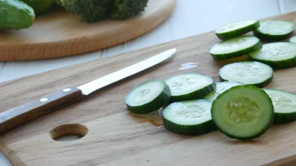 Darabolt uborka darabok egy fából készült konyhaasztalon. Egészséges vegán ételek.