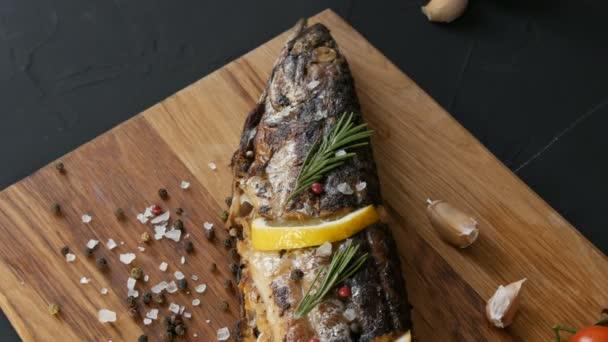 Finom friss hal, füstölt makréla fa aprítódeszkán a cseresznye paradicsom mellett, fokhagyma, durva só és bors, citromszeletekkel és zöld rozmaringos sprigkkel díszítve