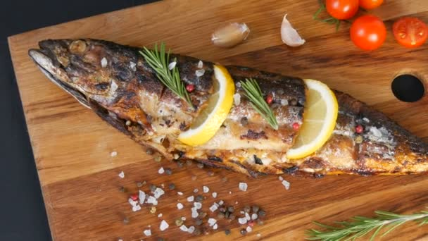 Delicious fresh fish, smoked mackerel on a wooden chopping board next to the cherry tomatoes, garlic, coarse salt and pepper, decorated with lemon slices and sprigs of green rosemary