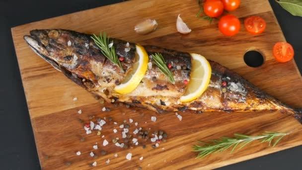 Lahodná čerstvá ryba, uzená makrela na dřevěné sekací desce vedle cherry rajčat, česnek, hrubá sůl a pepř, zdobená plátky citronu a smrky zelené rozmarýny