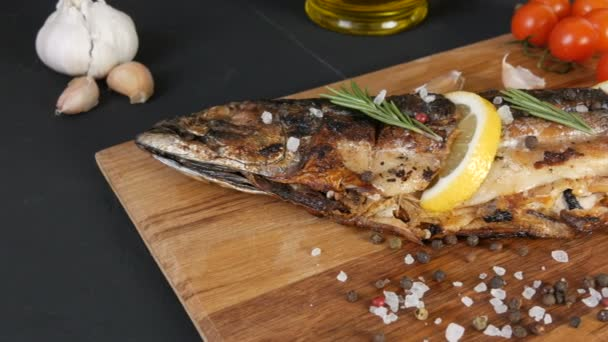 Delicious fresh fish, smoked mackerel on a wooden chopping board next to the cherry tomatoes, garlic, coarse salt and pepper, decorated with lemon slices and sprigs of green rosemary and olive oil