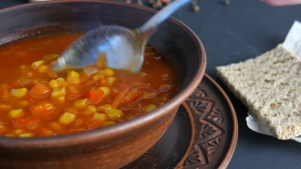 Horká pouze vařená červená rajčatová polévka s kukuřicí, která je smíchána se lžící v hnědém hliněném talíři v rustikálním stylu