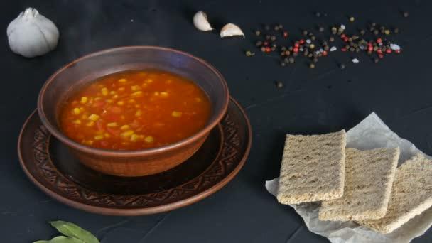 Horké červené rajče vegetariánská polévka se zeleninou a kukuřicí v hliněné vinobraní talíř na černém pozadí v rustikálním stylu