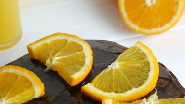 Hausgemachter Schokoladenkuchen mit Zuckerguss und Orangenscheiben neben Saft in einer weißen Küche