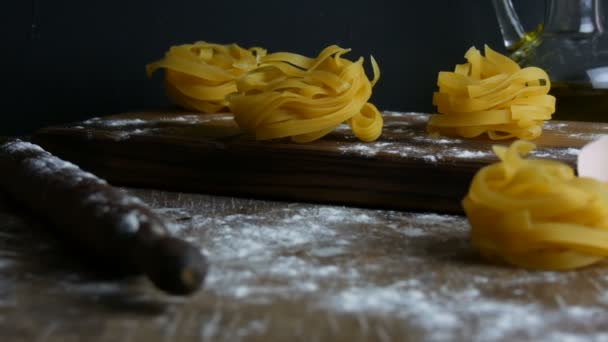 Italian rolled fresh fettuccine pasta. Spaghetti Tagliatelle nests on a wooden kitchen board next to a broken egg yolk, flour and olive oil in a rustic style. National italian food