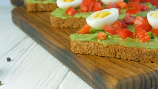 Gesunde vegane Ernährung. Pürierte Avocado auf geröstetem, mit schwarzem und rotem Pfeffer bestreutem braunem Brot verteilen. Leckerer Avocado-Toast zum Frühstück. Bruschetta mit Kirschtomaten und Wachteleiern kochen.