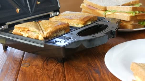 Morning breakfast in the home kitchen. Sandwiches with bacon, cheddar cheese and lettuce are fried in a special toaster or a sandwich maker. Special kitchen spatula takes fresh sandwich bread