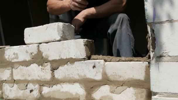 Mužské ruce stavitele ležely cihlou na čerstvém mokrém betonu. Řada bílých cihel na staveništi zblízka. Zeď