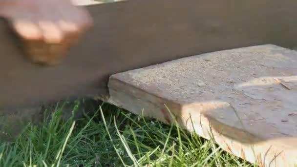 Alte rostige Metallhandsäge schneidet Holz aus nächster Nähe