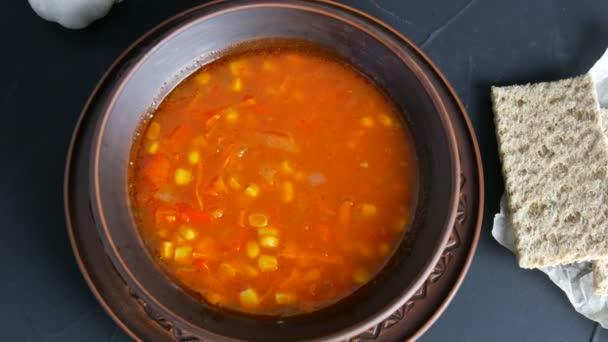 Top pohled na horké červené rajče vegetariánská polévka se zeleninou a kukuřicí v hliněné vinobraní talíř na černém pozadí v rustikálním stylu