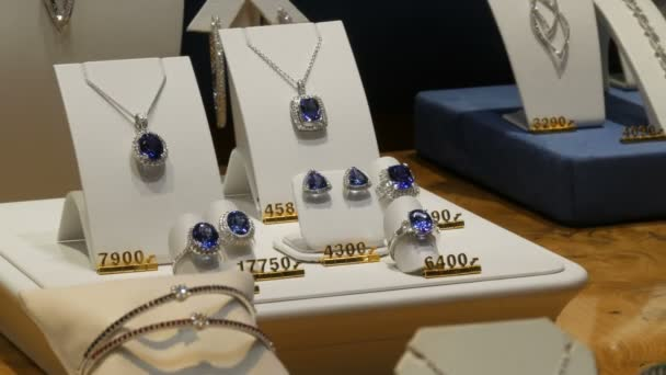 Expensive elite jewelry on the counter of jewelry store. Various diamonds, sapphires, white gold in earrings, bracelets, rings, necklaces with price tags