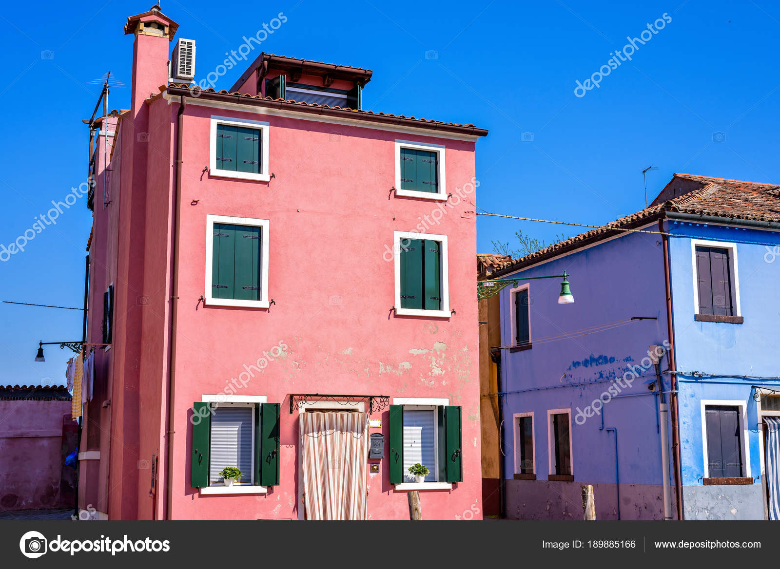 Daylight view to vibrant colorful pink and blue houses facades ...
