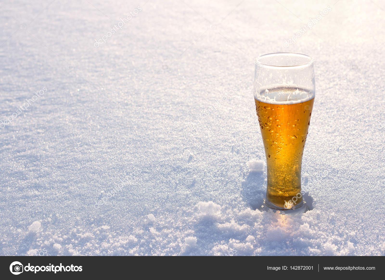 Krug Bier vom Fass im Schnee bei Sonnenuntergang. Schönen Winter ...