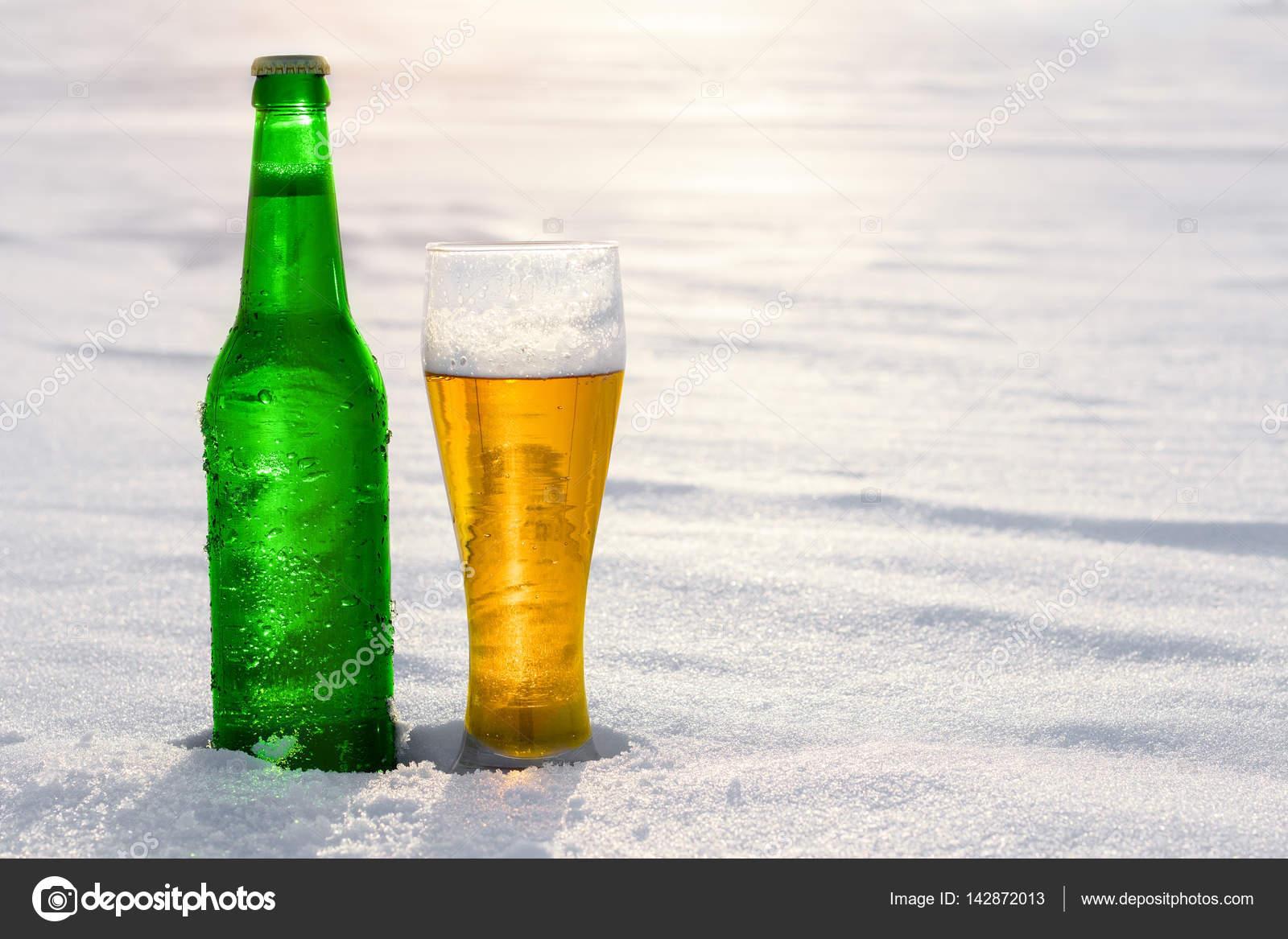 Becher und eine Flasche Bier vom Fass im Schnee bei Sonnenuntergang ...