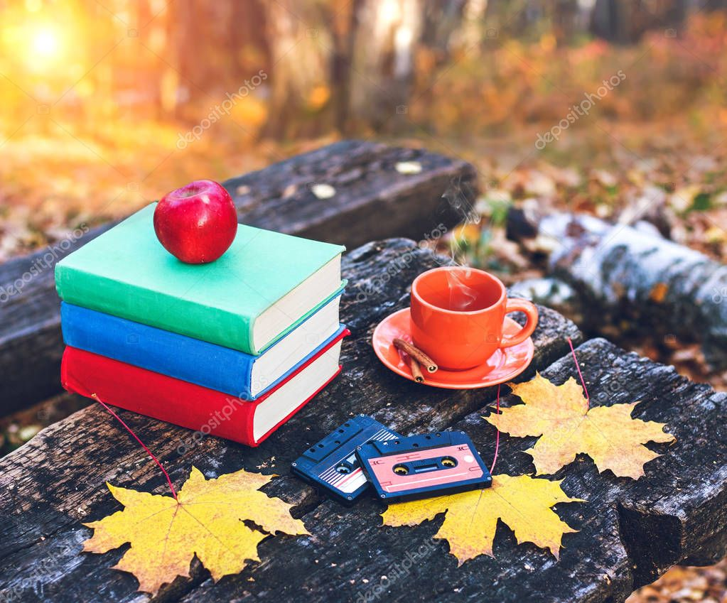 Фотообои Books and a cup of hot coffee with cinnamon on the table in the forest at sunset. Vintage style. Back to school. Education concept. Beautiful autumn background. Weekend in the park.