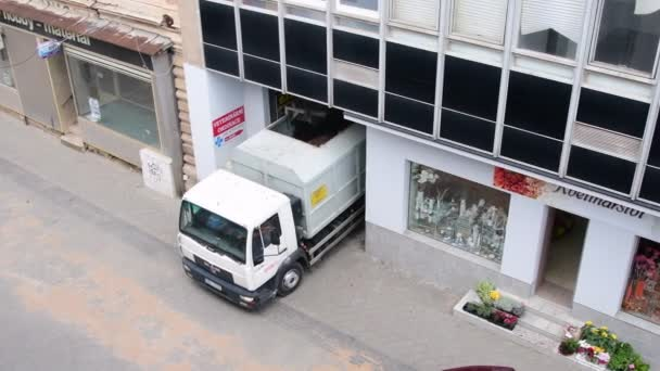 Nákladní auto se pohybuje dopředu z městské budovy