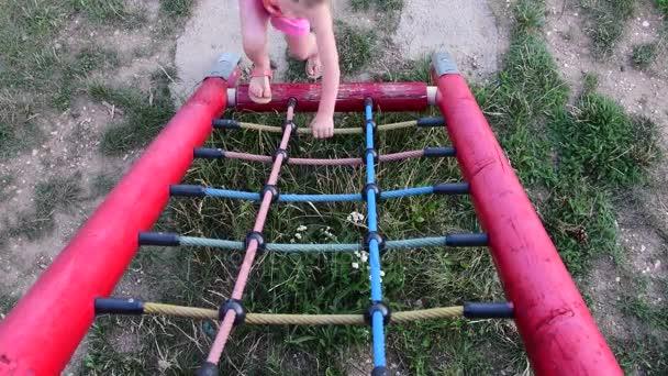 Malá holčička hraje na hřišti. Malá holka na lezení rámu. Dívka na Prolézačky