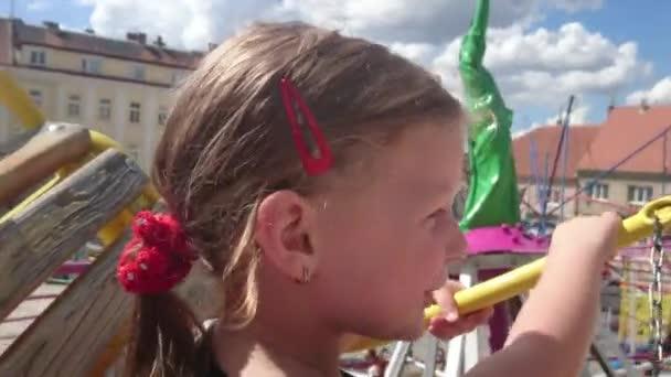 Roztomilá malá dívka na pouťových atrakcí. Lunaparky kolotoč. Křik při jízdě kolotoč veselá šťastná dívka. 4k.