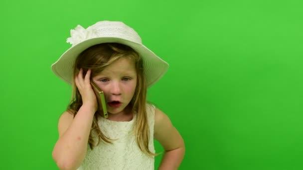 Roztomilá malá dívka používá mobilní telefon na chroma key pozadí. Malá dívka oblečená v romantických šatech. Bílý klobouk a svatební šaty. Chroma key pozadí