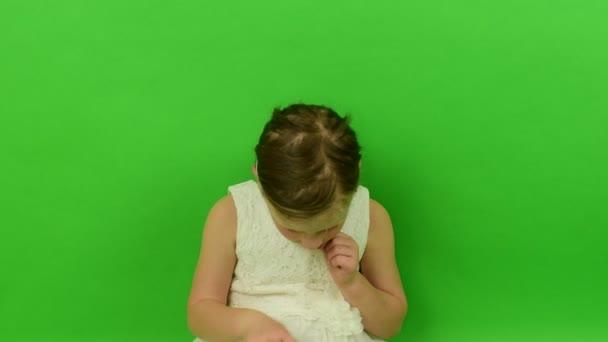 Roztomilá malá dívka používá mobilní telefon na chroma key pozadí. Malá dívka oblečená v romantických šatech. Bílé svatební šaty. Chroma key pozadí
