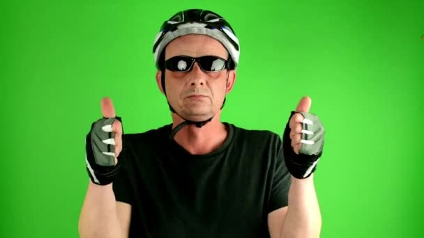 Mature mid aged man. Portrait of a mature cyclist in front of green screen. Man wears sunglasses, sport helmet and cycling gloves.