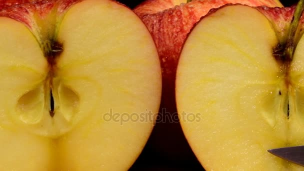 Organic red apples covered in water drops, refreshing juicy fruit, healthy diet. Black background. Apples cut in two.