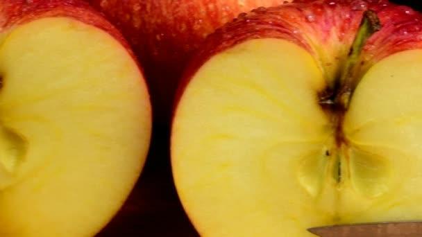 Bio červená jablka, na které se vztahuje kapky vody, osvěžující šťavnaté ovoce, zdravá strava. Černé pozadí. Jablka řez ve dvou. Nůž a prkénko.
