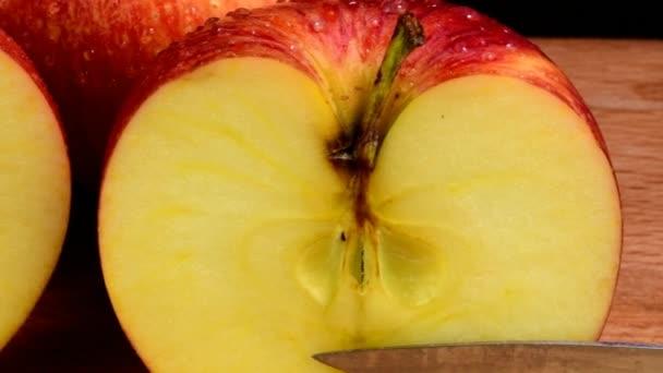Szerves piros Alma szereplő vízcseppek, frissítő lédús gyümölcs, egészséges táplálkozás. Fekete háttér. Alma vágni a kettő. Kés és a darabolás.