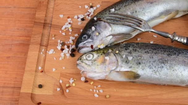 Fresh raw rainbow trouts with spices and fork on wooden board. Healthy food and dieting concept. Close-up