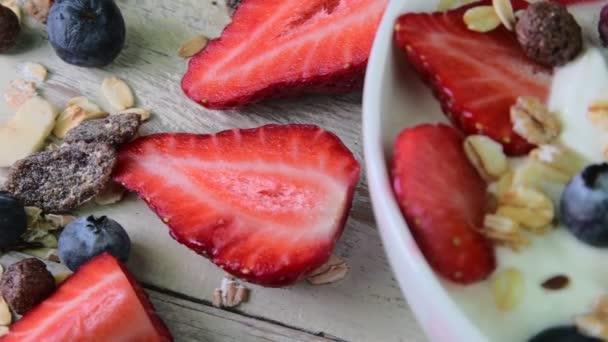 Zdravá snídaně, cereálie s jogurtem, jahody, borůvky, maliny a müsli na dřevěné rustikální pozadí. Koncept: fitness, strava, wellness a snídaní