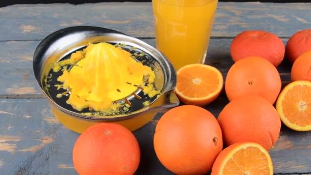 Tangerines, oranges, a glass of orange juice and manual citrus squezeer on blue wooden background. Oranges cut in half